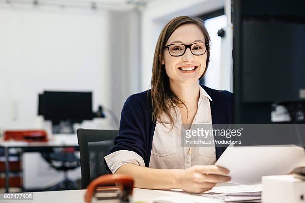casual busineswoman smiling at a desk in an office - mulher de negócios - fotografias e filmes do acervo