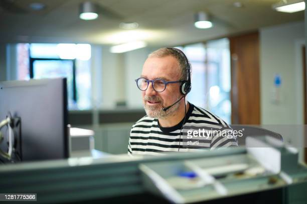 casual call centre worker - men stock pictures, royalty-free photos & images