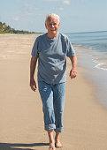 caucasian senior man age walking beach