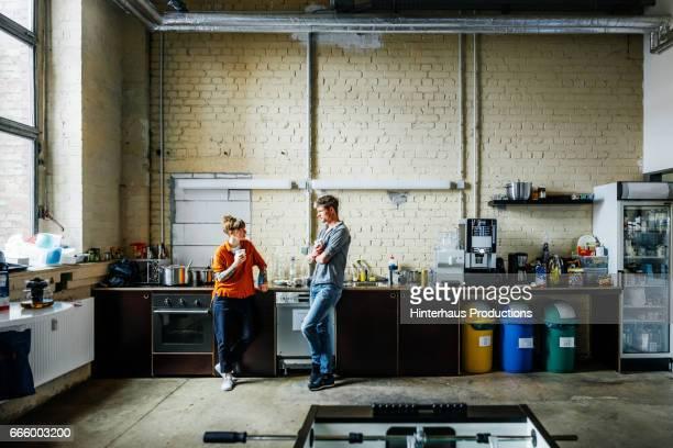 Casual colleagues having a break in office kitchen