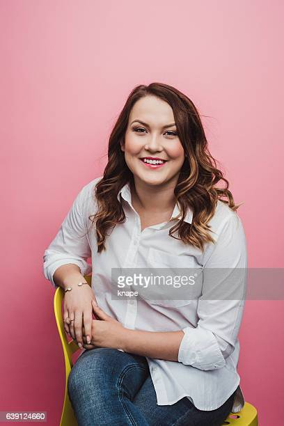 Casual cute young woman on pink