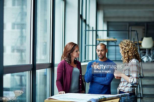 casual discussion between coworkers - three people stock pictures, royalty-free photos & images