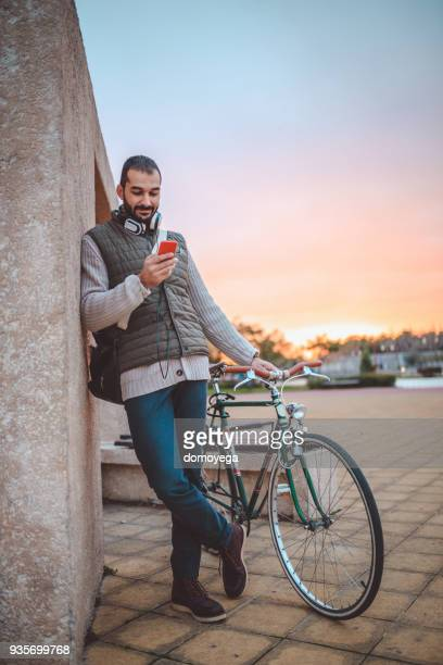 Casual dressed man with a bike using phone outdoors