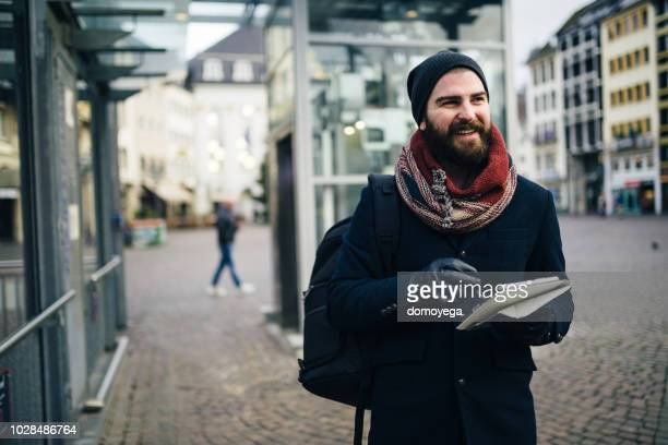 Casual dressed man with a digital tablet walking in the city street