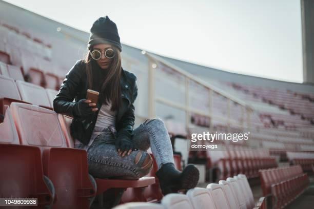 lässig gekleidete frau mit telefon im freien an einem sonnigen tag im stadion - liberty stadion stock-fotos und bilder