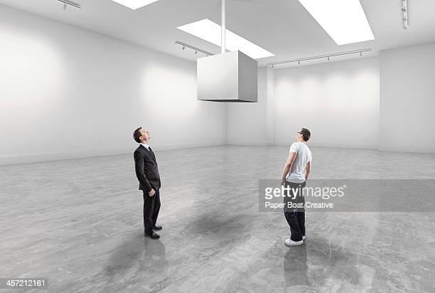 casual man and business man looking at blank cube - ausstellung stock-fotos und bilder