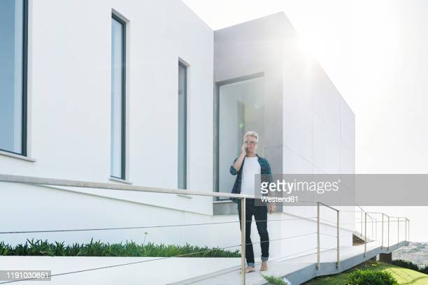 casual man outside his modern home talking on the phone - only mature men stock pictures, royalty-free photos & images