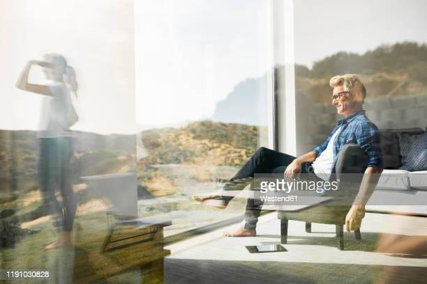 casual man sitting in modern home with woman standing in garden - erwachsener über 30 stock-fotos und bilder