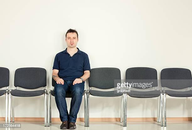 Casual homme assis sur la rangée de chaises