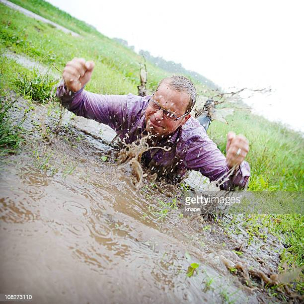 Casual man splashing in a puddle with mud