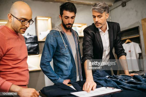 casual man standing in boutique with stylists and discussing new modern outfit in team - メンズウェア ストックフォトと画像