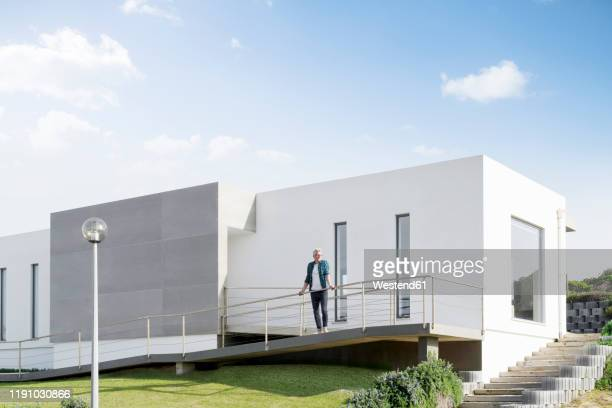 casual man standing in front of his modern home - only mature men stock pictures, royalty-free photos & images