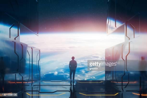 地球を見ている宇宙プラットフォームに立っているカジュアルな男 - 宇宙ステーション ストックフォトと画像