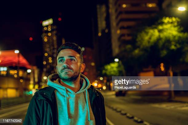 casual man wearing a jacket in the street at night - one man only stock pictures, royalty-free photos & images