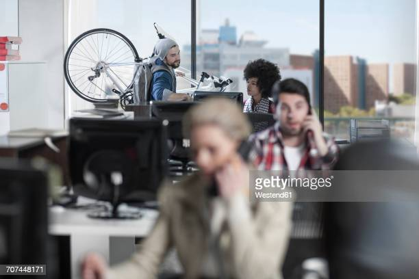 Casual man with bike in modern office talking to female colleague