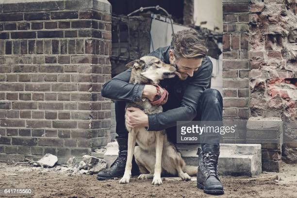 casual man with dog on a building site - loup blanc photos et images de collection