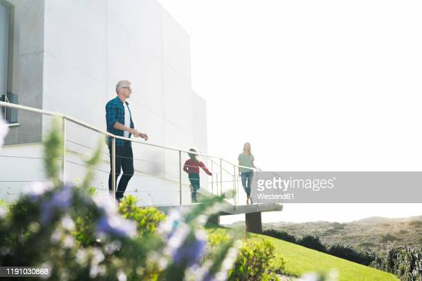 casual man with his family standing in front of modern home looking at the landscape - reichtum stock-fotos und bilder