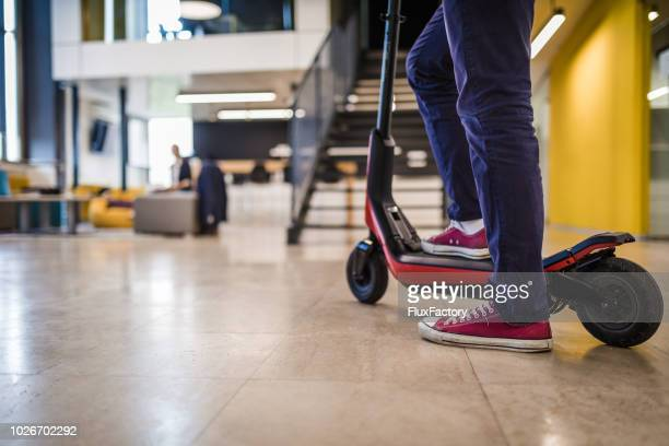 casual manager arriving to the office on his electric scooter - electric scooter stock pictures, royalty-free photos & images