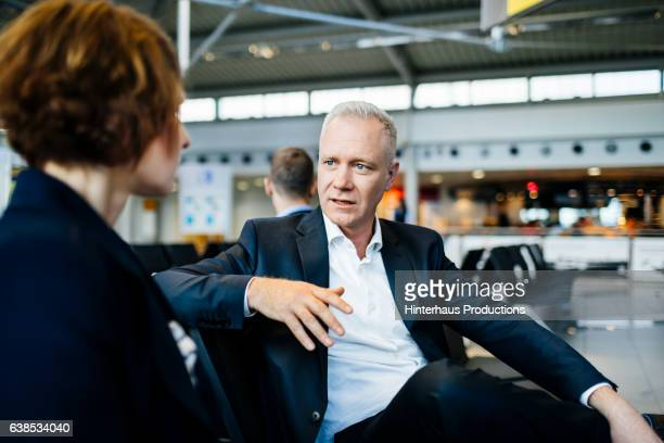 Casual mature businessman talking with a female colleague at the airport