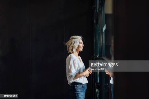 casual mature businesswoman looking out of window in loft office - belgium stock pictures, royalty-free photos & images