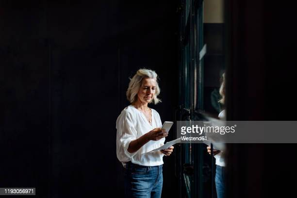 casual mature businesswoman using smartphone at the window in loft office - businesswear stock pictures, royalty-free photos & images