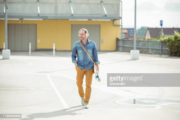 casual mature man with headphones and skateboard walking on parking deck - shoulder bag stock pictures, royalty-free photos & images