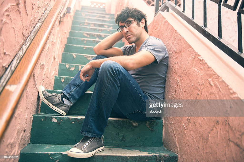 Casual Miami Man in 20s Sitting in Contemplation on Stairs : Stock Photo