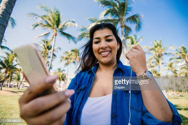 casual millennial latina enjoys summer in usa and using smart phone with headphones - of miami photos stock pictures, royalty-free photos & images