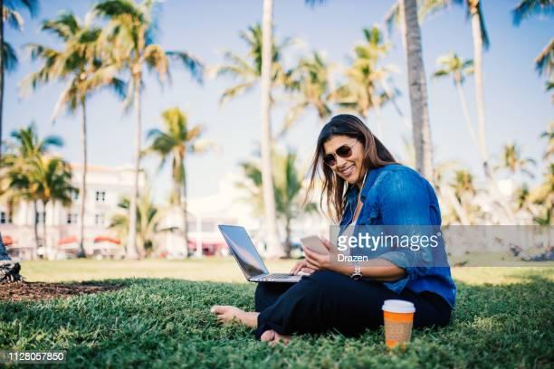 latina milenaria ocasional uso de laptop en parque en estados unidos - modelos gorditas fotografías e imágenes de stock