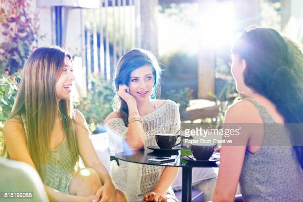 casual moment of three friends talking in a coffee shop outdoors - pavement cafe stock pictures, royalty-free photos & images