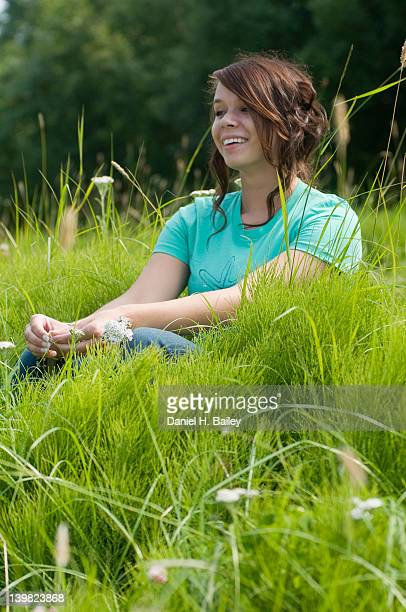 Casual portrait of an 18-year old teen girl, smiling and sitting in a patch of tall green grass and wildflowers in the sunshine, Anchorage, Alaska