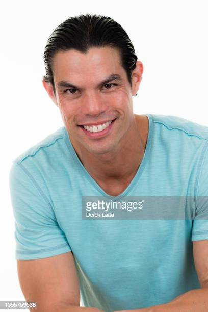 Casual portrait of attractive Asian-Hispanic male in blue t shirt smiling'n
