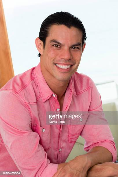 Casual portrait of happy and attractive Asian American man smiling indoors'n