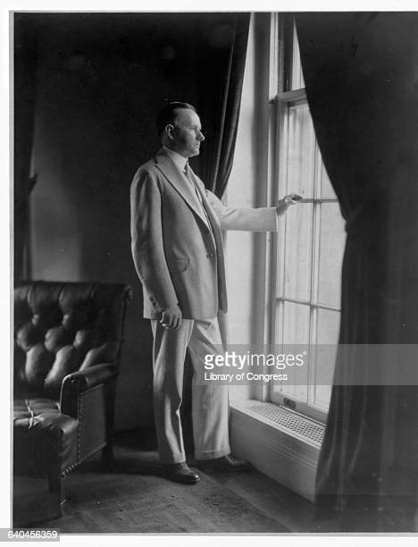 A casual portrait of President Calvin Coolidge looking out a window during his time in office