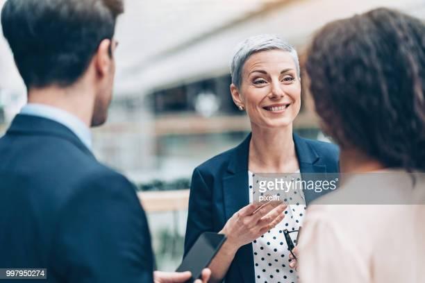 casual gesprek tussen bedrijfspersonen - wet stockfoto's en -beelden