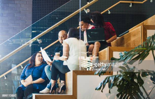 casual team meeting side view. - cultures stock pictures, royalty-free photos & images