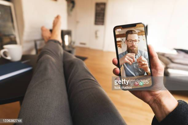 casual video call meeting on a smartphone from home - human hand stock pictures, royalty-free photos & images