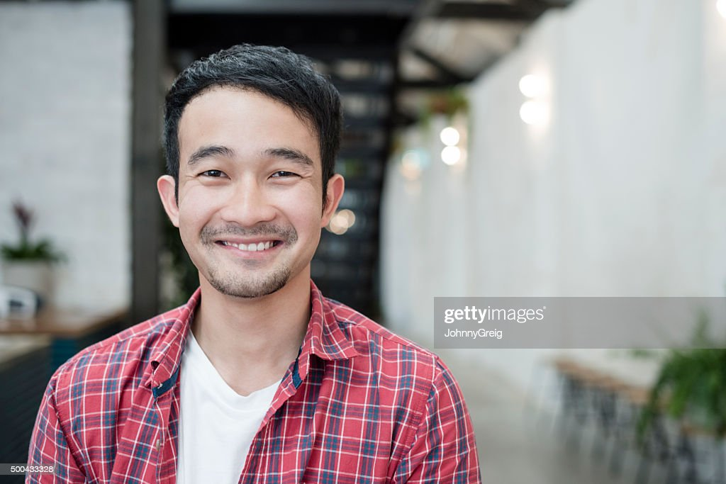 Casual young Asian businessman smiling towards camera, portrait : Stock Photo