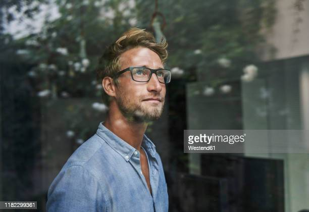 casual young businessman behind windowpane in office - beschaulichkeit stock-fotos und bilder