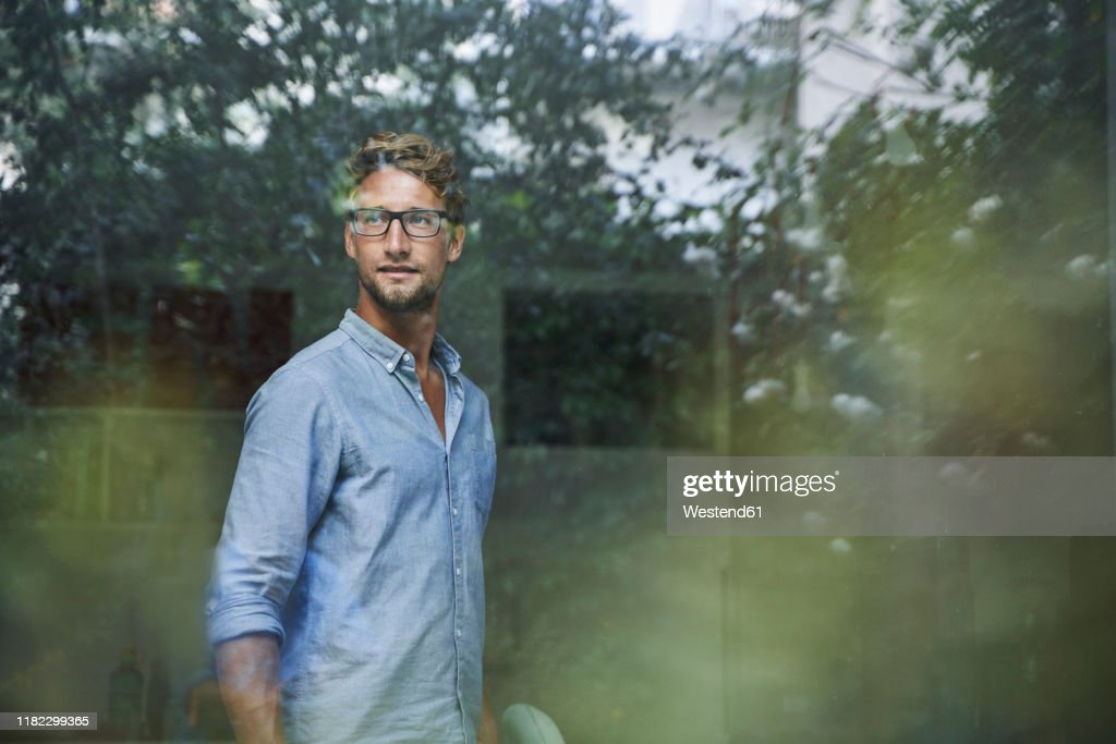 Casual young businessman behind windowpane in office : Stock Photo