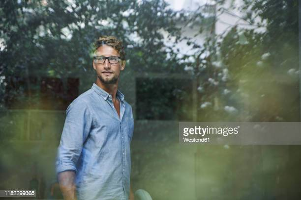 casual young businessman behind windowpane in office - spiegelung stock-fotos und bilder