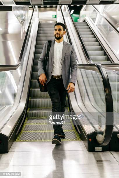 casual young businessman on escalator - striding stock pictures, royalty-free photos & images