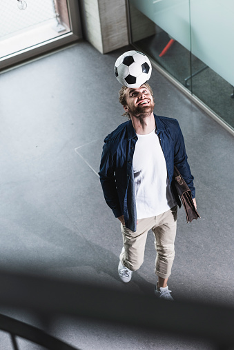 Casual young businessman playing football in office - gettyimageskorea