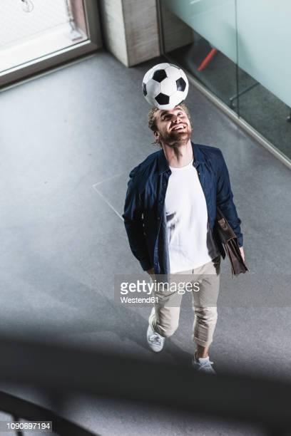 casual young businessman playing football in office - spiel sport stock-fotos und bilder