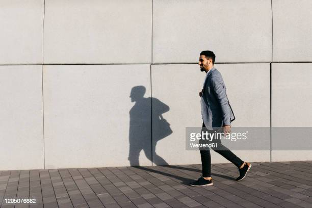 casual young businessman walking along the wall in the city - white jacket stock pictures, royalty-free photos & images
