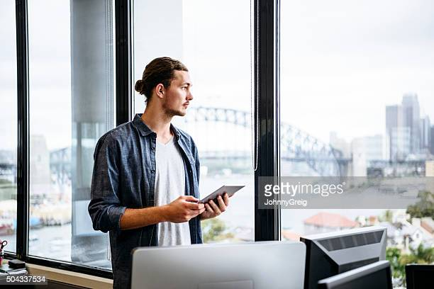 casual young businessman with tablet by window in modern office - sydney stock pictures, royalty-free photos & images