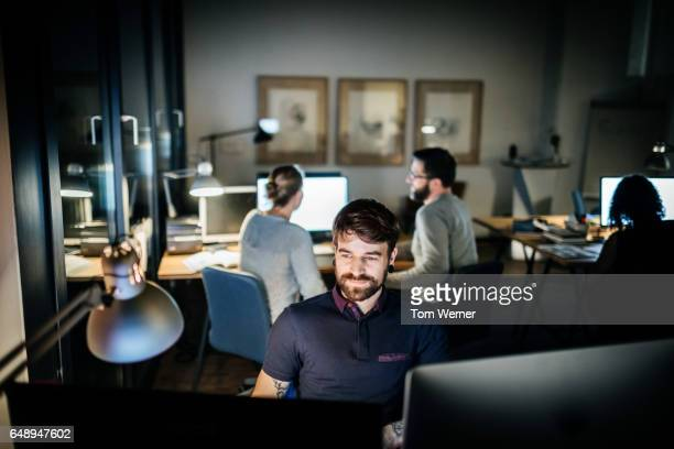Casual young businessman working late on a computer