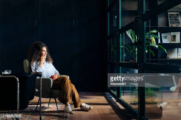 casual young businesswoman looking out of window in loft office - one young woman only stock pictures, royalty-free photos & images