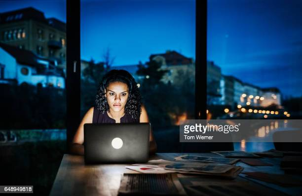 Casual young businesswoman working late on a laptop