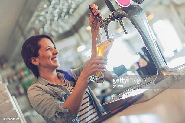 Casual young cheerful female bartender pouring beer from facet